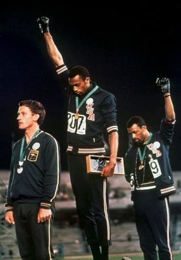 """Powerful moment: Australia's Peter Norman (left) joins American athletes Tommie Smith and John Carlos on the podium during the famous """"Black Power"""" demonstration."""