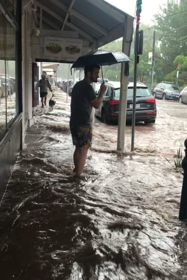 A man ankle-deep in floodwaters in Flemington.
