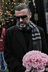 In this 2011 photo, George Michael leaves his house in north London after recovering from a life-threatening bout  of pneumonia.