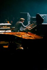 Nils Frahm on stage with his assortment of instruments.