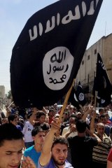 Supporters fly a Islamic State flag in Mosul in 2014.