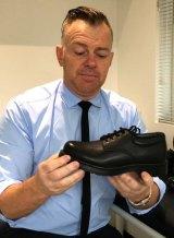 Brendan Brown, of A Step Ahead Podiatry, examines a school shoe.