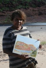 Lenie Namatjira with one of her paintings at Finke River.