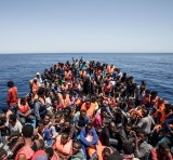 Migrants crowd the deck of their wooden boat off the coast of Libya May 14, 2015.