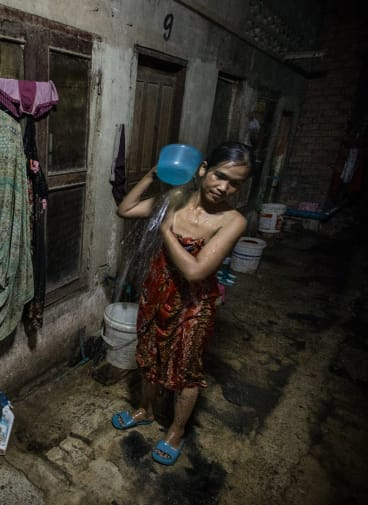 Oem Mom, 33,  sleeps on a wooden bench with four other family members in a tiny room  off a dank alleyway near the Phnom Penh factory where she works.