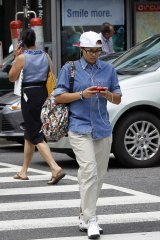 A pedestrian text messages while crossing the street in downtown Washington. A New Jersey legislator is targeting distracted walking.