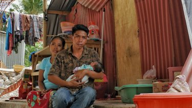 Hanan holds baby Akila, his wife Reniatun behind him, in their makeshift home.