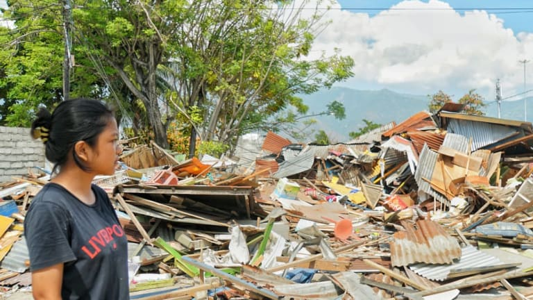 Ayu looks at the ruble left byt he tsunami at Talise, Palu.