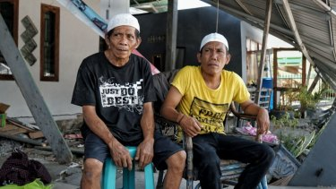 Tamrin, left, with his son Bobi in front of his damaged house.