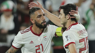 Iran midfielder Ashkan Dejagah (left) celebrates with teammate Sardar Azmoun.