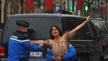 A topless protester gets close to US President Donald Trump's motorcade in Paris.