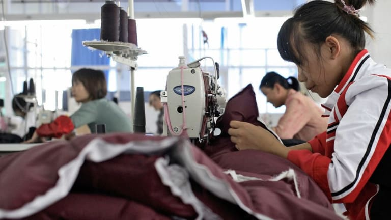 Workers sow down jackets together at the Quanli Garment Factory in Pinghu, Zhejiang Province, China.
