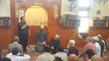A police officer addresses worshipers at Friday prayers at a mosque in Heidelberg.