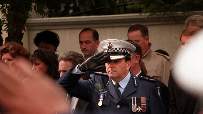 Chief Commissioner Neil Comrie salutes Gary Silk on his last journey.