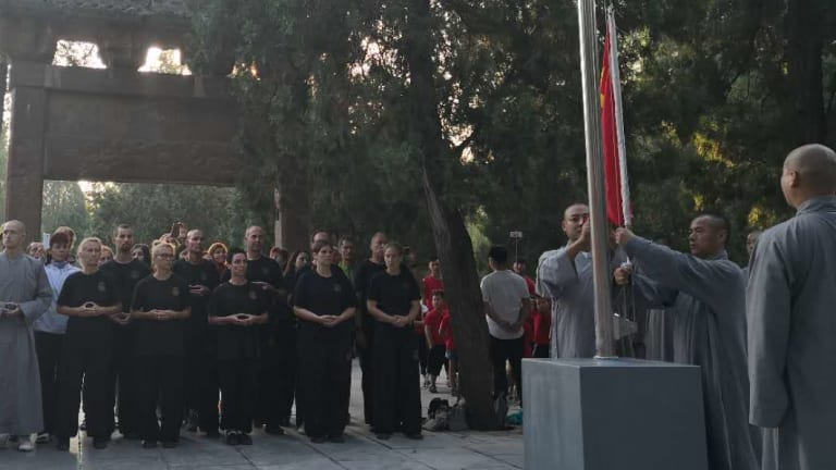 """Foreign """"disciples"""" attend the flag-raising ceremony."""