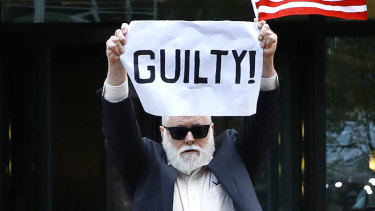 Protester Bill Christeson holds up a sign as the first count of guilty comes in.