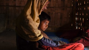A Rohingya woman with her orphaned granddaughter at a refugee camp in Bangladesh.