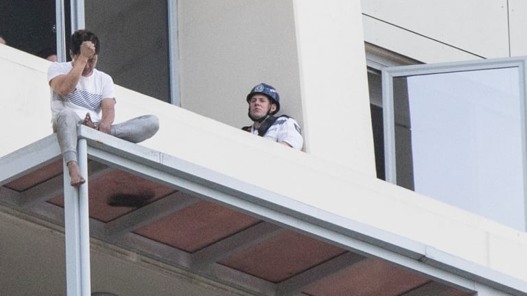 Police speak to June Oh Seo on the awning of a Chatswood high-rise building.