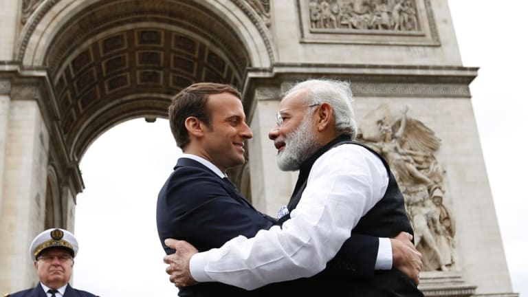 Indian Prime Minister Narendra Modi hugs French President Emmanuel Macron, at the Arc de Triomphe in Paris. The pair put forth a common front on the need to fight climate change.