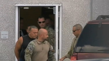 This frame grab from video provided by WPLG-TV shows FBI agents escorting Cesar Sayoc, in sleeveless shirt.