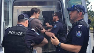 The man is led into a police van after police asked him to move on repeatedly before pulling him away from the protest.