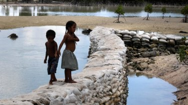 A sea wall in the Kiribati village of Tebunginako at low tide. The formerly freshwater lagoon is inundated with sea water due to rising seas and erosion.