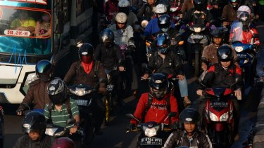 Cars, buses and motorcycles sit in congested traffic in the business district in Jakarta.