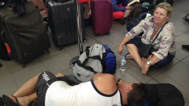 Confusion and fatigue: passengers stranded at Sydney Airport.