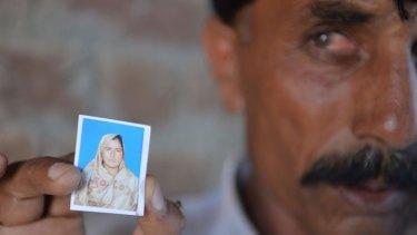 Twice widowed: Pakistani Mohammad Iqbal   holds up an image of his wife Farzana Parveen.