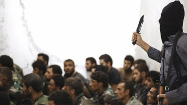 An IS militant stands over captured Syrian army soldiers and officers in August last year.