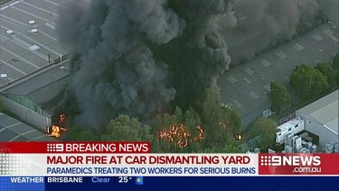 A huge plume of smoke rises from the blaze at the car wrecking yard in Revesby in Sydney's south-west.