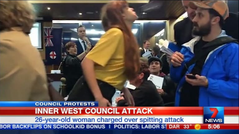 Cartoonist Nicola Minus has been charged with spitting on Richard Pearson, the newly appointed head of the Inner West Council during a protest against council amalgamations.