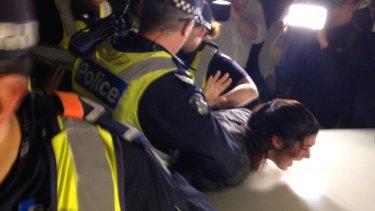 Police arrest a protester.