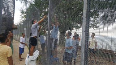 Manus Island refugees are securing damaged perimeter fences at the processing centre against possible attacks.