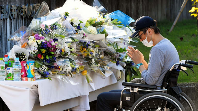 A man prays at a makeshift altar in front of the Tsukui Yamayuri En care centre for the disabled in Sagamihara, Japan.