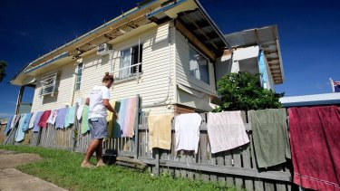 Lucas Patchett of charity laundry service Orange Sky hangs out some washing in front of a Yeppoon home damaged by Cyclone Marcia.