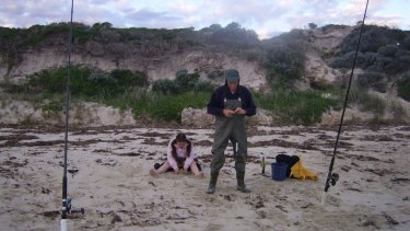 Ms Clifton's father and niece fish on the remains of the beach, with its former height seen in the background.
