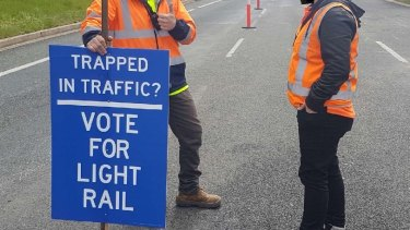 Road workers hold pro-light rail signs in Woden.