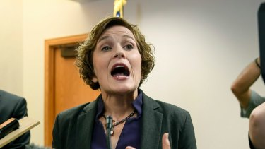 Minneapolis Mayor Betsy Hodges tries to talk to the media as she is shouted at by protesters demanding her resignation on Friday.