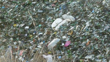 Plastic and other rubbish is mixed up in the unwashed recycled glass.