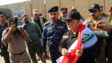 Iraq's Prime Minister Haider al-Abadi holds a national flag upon his arrival in Mosul.