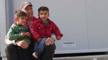 Don Johnson from the Red Cross at Greek-Macedonian border with two refugee children.