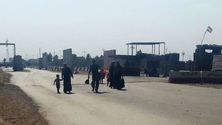 Shift: Residents flee Iraq's northern city of Mosul in July, walking towards nearby Erbil.