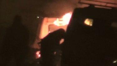 Two unidentified armed men approach a burning vehicle near a hotel in Ouagadougou, Burkina Faso.