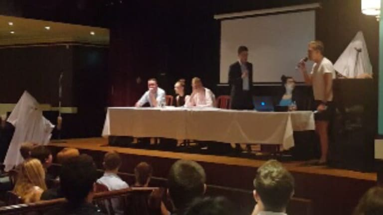 Two men dressed in white hoods and white linen interrupted the Young Liberal council meeting in Sydney.