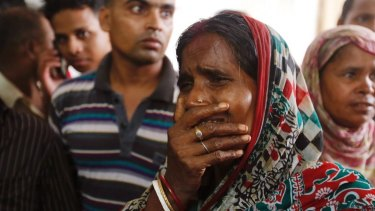 A relative of a fire victim cries as victims' bodies are carried into a makeshift morgue.