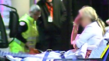 Paramedics help a woman after the Inflation nightclub shooting.