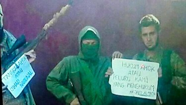 """Members of the Syria-based jihadist group Jabhat Fatah al-Sham hold a sign that reads """"Punish Ahok or our bullets will""""."""