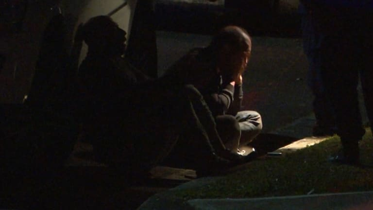 Two men sit in the gutter after a girl was shot dead in Lalor Park.