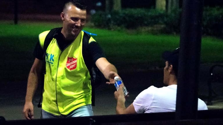 Take Kare Ambassador coordinator Nate Brown offers a bottle of water to a late-night reveller.